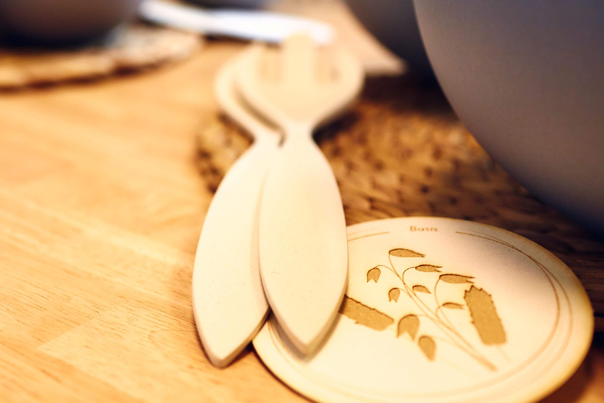 Zwei Holzlöffel liegen auf einem Tisch neben einer Bowl